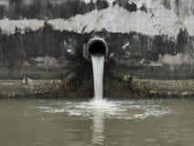 Schmutziger Abfluss, der einen Fluss verunreinigt Lizenzfreies Stockbild