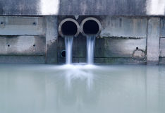 Schmutziger Ablaß, der einen Fluss beschmutzt Lizenzfreie Stockfotografie
