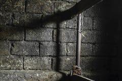 Schmutziger, dunkler, gespenstischer, furchtsamer und mystischer Bauernhof-Raum für die Kühe mit sichtbarem hängendem Rusty Chain stockbilder