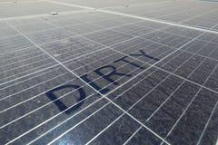Schmutziger Dusty Solar Panels mit dem Text SCHMUTZIG lizenzfreie stockbilder