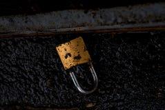 Schmutziger gebrochener Goldverschluß auf der schwarzen Straße Stockfotos
