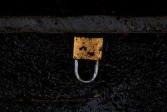 Schmutziger gebrochener Goldverschluß auf der schwarzen Straße Stockfotografie