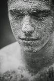 Schmutziger Gesichtsmann des Schlammes Stockfoto