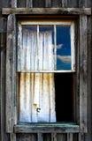 Schmutziger heftiger Vorhang am rustikalen unfertigen hölzernen Fenster - angesehen von der Außenseite stockfotografie