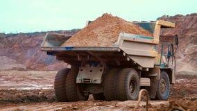 Schmutziger Kippwagen transportiert Sand auf Straße im Steinbruch Großer gelber Kipper-LKW stock video footage