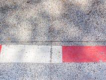 Schmutziger konkreter Boden mit weißer und roter Linie Stockbild