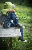 Schmutziger obdachloser Junge des Fotos mit heftigen Jeans Stockfoto