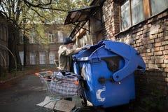 Schmutziger obdachloser Mann, der nach Lebensmittel im Abfalleimer sucht Lizenzfreies Stockbild