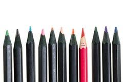 Schmutziger roter Bleistift und schwarze Bleistifte auf weißem Hintergrund Lizenzfreie Stockfotos