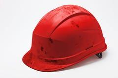 Schmutziger roter Schutzhelm Stockfotografie