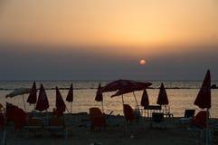 Schmutziger sandiger Strand, gefüllt mit roten Sonnenschirmen und Stühlen des Plastikabfalls im Sommersonnenuntergang stockfotografie