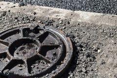Schmutziger verrosteter Abwasserkanalkanaldeckel auf einem Straßenrand Stockfotos