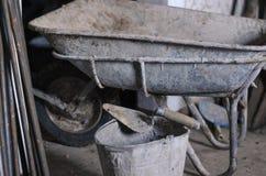Schmutziger Zementschubkarrewarenkorb an der Baustelle mit unfertigem Zementwandhintergrund Stockfoto