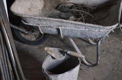 Schmutziger Zementschubkarrewarenkorb an der Baustelle mit unfertigem Zementwandhintergrund Lizenzfreie Stockfotos