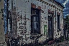 Schmutziges altes Haus, das auseinander an der Dämmerung mit bewölktem Himmel fällt lizenzfreie stockfotografie