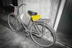 Schmutziges altes pushbike, das an der Wand in der Hintergasse mit Brigg sich lehnt Stockfotos