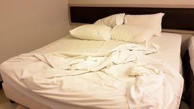 Schmutziges Bett mit Kissen und Decke im Raum Stockbild