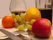 Schmutziges Geschirr und Glas mit Wein, Obst und Gemüse Stockfotografie