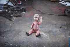 Schmutziges nacktes Plastikbaby - Puppe, die aus den Grund vor einem Metallshopwellenartig bewegen sitzt stockbilder