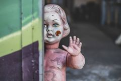 Schmutziges nacktes Plastikbaby - Puppe, welche die Tür am schauenden Metallshop unheimliche und gejagte spinnende Nahaufnahme be stockfotografie