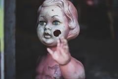 Schmutziges nacktes Plastikbaby - Puppe, welche die Tür am schauenden Metallshop unheimliche und gejagte spinnende Nahaufnahme be stockfoto