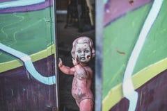 Schmutziges nacktes Plastikbaby - Puppe, welche die Tür am schauenden Metallshop unheimliches und gejagtes Spinnen bereitsteht stockfotos