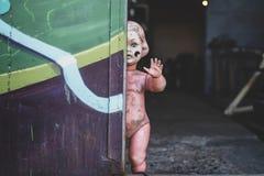 Schmutziges nacktes Plastikbaby - Puppe, welche die Tür am schauenden Metallshop unheimliches und gejagtes Spinnen bereitsteht stockfoto
