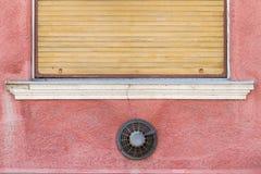 Schmutzwand mit gelbem Fensterladen Stockfotografie
