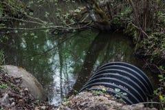 Schmutzwasser stammt das Rohr ab, das den Fluss verunreinigt Lizenzfreies Stockfoto
