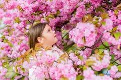 Schn?ffelnblumen Werden Sie Saisonallergie los M?dchen, das Blumenaroma genie?t Pollenallergiekonzept Kind auf rosa Blumen lizenzfreies stockbild