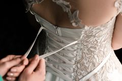 Schn?ren des Hochzeits-Kleides lizenzfreie stockbilder