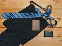 Schnallen Sie Hose mit Aufhänger um und binden Sie auf hölzernem Hintergrund lizenzfreie stockfotografie