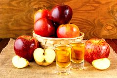 Schnapps drinks and apples in the wicker basket Royalty Free Stock Images