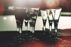 Schnapsgläser im Nachtklub, gefüllt mit den klaren und dunklen alkoholischen Getränken stockbilder
