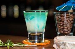 Schnapsglas mit blauem Alkoholgetränk auf getrockneter orange Scheibe mit Rosmarin nahe Glas mit Kaffeebohnen lizenzfreie stockfotografie