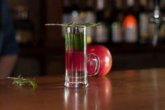Schnapsglas mit mehrfarbigem Alkoholgetränk und Rosmarin auf nahem rotem Apfel lizenzfreies stockfoto