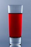 Schnapsglas mit rotem Cocktail nach innen auf Glas mit eigener Reflexion Lizenzfreies Stockbild