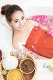 Schöne asiatische Schönheitsfrau im Bad mit dem rosafarbenen Blumenblatt Körperpflege und Badekurort Lizenzfreies Stockfoto