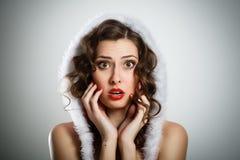 Schöne überraschte Frau, die Weihnachtsmann-Kleidung trägt Lizenzfreies Stockfoto