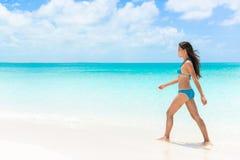 Schöne Bikinifrau, die auf weißen Sandstrand geht Lizenzfreie Stockbilder