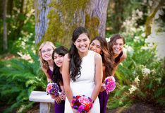 Schöne biracial junge Braut, die mit ihrem multiethnischen grou lächelt Stockbild