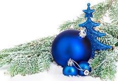 Schöne blaue Weihnachtsbälle auf eisigem Tannenbaum Eine Abbildung einer blauen Blumenverzierung mit Schatten Lizenzfreie Stockbilder