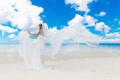 Schöne blonde Braut im weißen Hochzeitskleid mit großem langem Weiß Stockfotografie