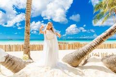 Schöne blonde Braut im weißen Hochzeitskleid mit großem langem Weiß Stockbilder