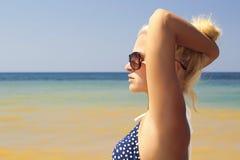 Schöne blonde Frau auf dem Strand in der Sonnenbrille Stockfotografie