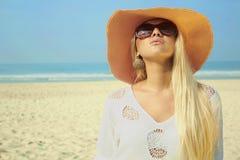 Schöne blonde Frau auf dem Strand im Hut und in der Sonnenbrille Stockfoto