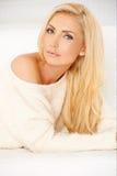 Schöne blonde Frau, die auf Sofa liegt Stockfotografie