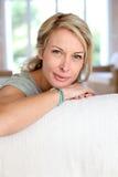 Schöne blonde Frau, die auf Sofa sich lehnt Lizenzfreies Stockfoto