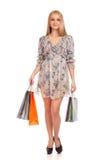 Schöne blonde Frau, die Einkaufstaschen anhält Stockfoto