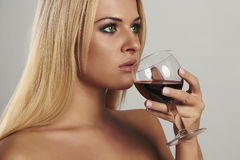 Schöne blonde Frau, die Rotwein trinkt Make-up pretty adult girl with alcohol Stockbild